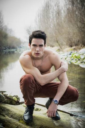 naked abs: Handsome fit shirtless young man sitting on his heels next to water pond or river, looking at camera Stock Photo