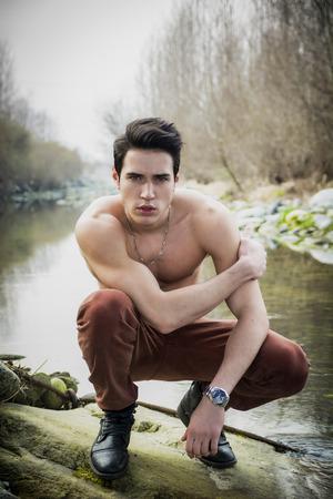 hombre desnudo: Joven sin camisa ajuste hermoso que se sienta sobre sus talones junto al estanque de agua o r�o, mirando a la c�mara