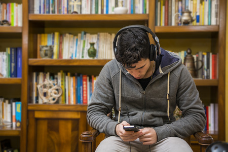 Attractive young man sitting listening to music on a set of stereo headphones in his study in front of a bookcase filled with books photo