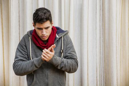 resfriado: Hombre joven enfermo con gripe o resfriado vistiendo bufanda y ropa de invierno. Tiro de interior en casa Foto de archivo