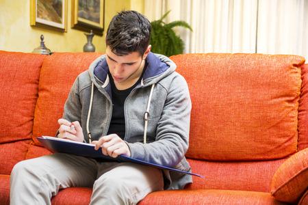 � writing: Apuesto joven en casa escribiendo en el cuaderno, sentado en el sof� Foto de archivo