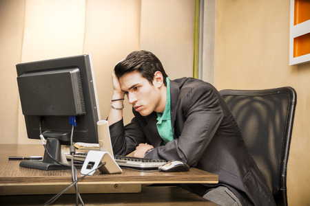 Preoccupied, worried young male worker staring at computer screen in his office photo