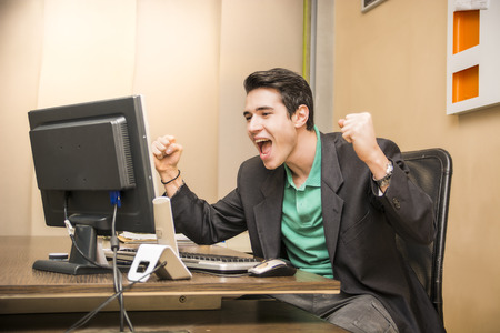 businessman working at his computer: Happy young businessman screaming for joy, sitting at desk in his office working with computer