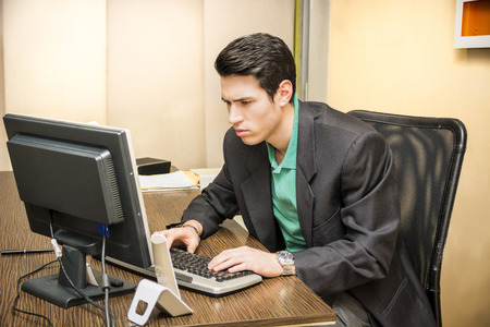 Serious handsome young businessman sitting at his desk in the office working at computer photo
