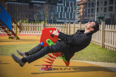 Hombre joven revivir su infancia que navegan en un montar a caballo parque infantil en un asiento rojo colorido de la primavera con una sonrisa de felicidad en un parque urbano