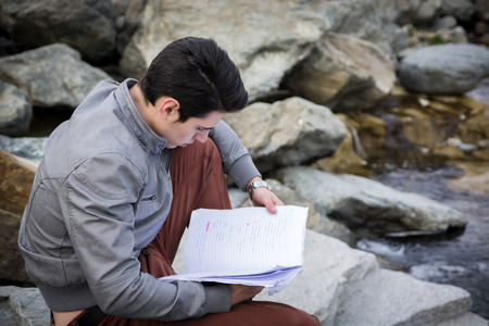 alongside: Young male student studying outdoors sitting on rocks alongside a stream reading his notes