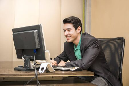 Successful handsome young businessman sitting at his desk in the office smiling and looking at the computer screen photo