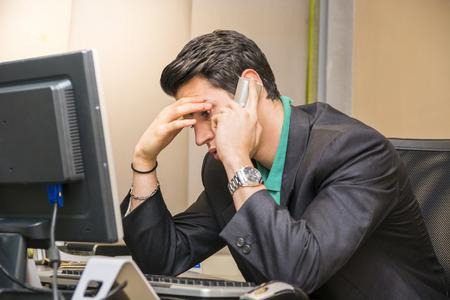 電話で話している忙しいオフィスで机に座って深刻な魅力的な若いビジネスマン
