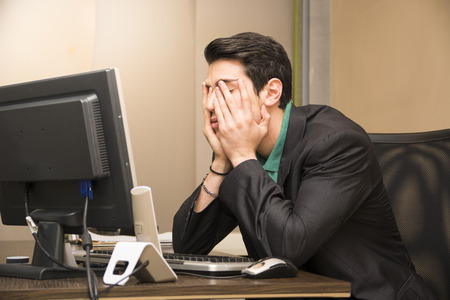 gente triste: Cansado joven hombre de negocios aburrido sentado en su escritorio en frente de su equipo con la barbilla apoyada en las manos y los ojos cerrados