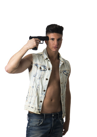 suicidal: Suicidal attractive young man in an unbuttoned shirt standing with a serious expression pointing a gun at his head isolated on white