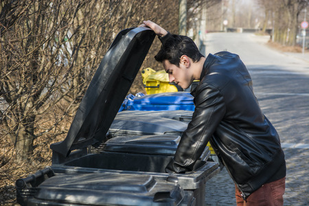 garbage bin: Attractive young man putting out rubbish standing with the lid up on a bin in a row of garbage bins at the side of a street