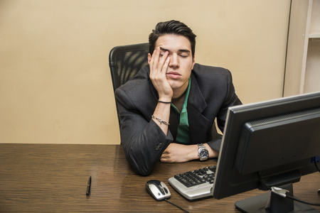 Tired bored young businessman sitting at his desk in front of his computer with his chin resting on his hand and eyes closed