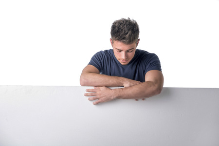 looking down: Handsome young man behind a blank horizontal white banner looking at copyspace, on white background Stock Photo