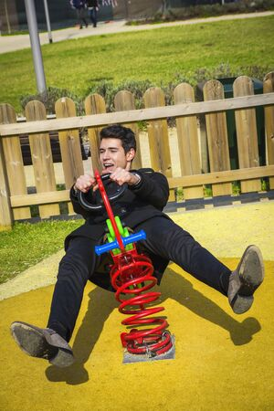 delirious: Young man reliving his childhood plying in a childrens playground riding on a colorful red spring seat with a happy smile in an urban park Stock Photo