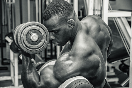 Hunky muscular black bodybuilder working out in gym, exercising biceps with dumbbell. Black and white photo Imagens
