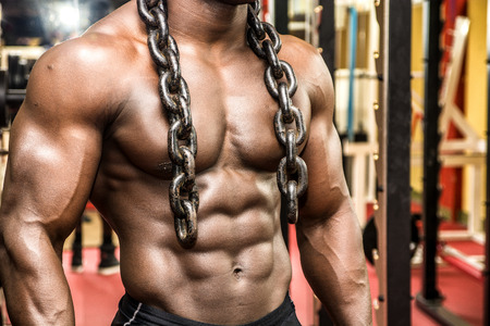 topless model: Attractive hunky black male bodybuilder doing bodybuilding pose in gym with iron chains over shoulders Stock Photo