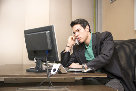 Successful handsome young businessman sitting at his desk in the office talking on phone photo