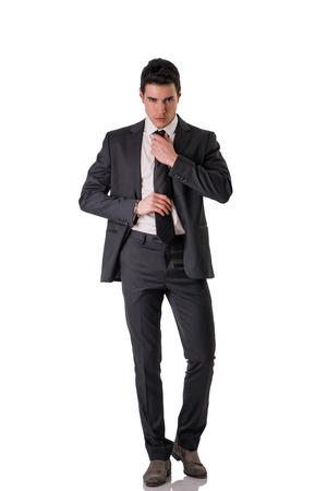 Figura completa foto de hombre elegante joven guapo con traje y la corbata, aislado en blanco, mirando a la cámara