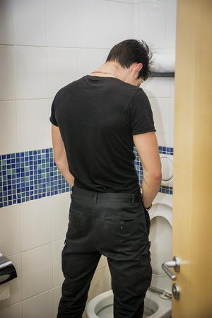 Rear View of a Young Man in Black Outfit Peeing at the Toilet Inside his Bathroom. Stock Photo