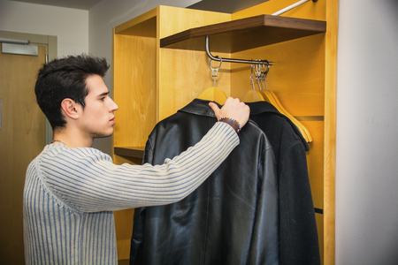 walk in closet: Serious Handsome Young Man Hanging his Black Coats at his Wardrobe Inside his Room.