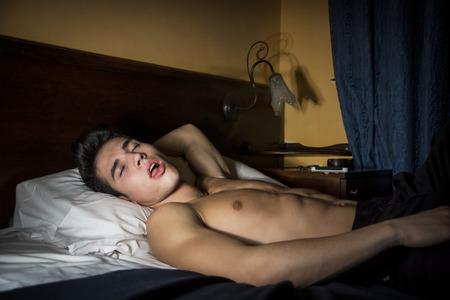 m�nner nackt: Handsome junger Mann mit nacktem Oberk�rper sportlich im Bett in der Nacht mit geschlossenen Augen, Schlaf