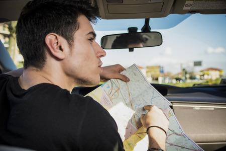 ゴージャスな若い男性の運転を保持地図求めての間見ている方向のフレームの右側に方向の車を閉じます。 写真素材