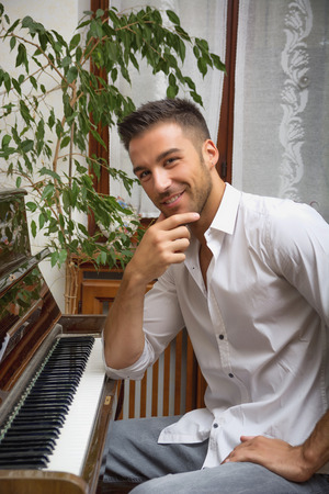 upright piano: Young handsome male artist sitting at his wooden classical upright piano, ready to play, smiling at camera, indoor portrait