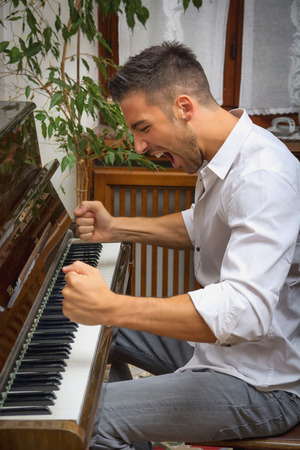 Young handsome male artist playing his wooden classical upright piano, shouting unhappy and frustrated Stockfoto