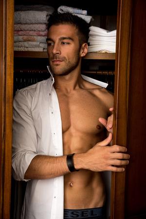 セクシーなハンサムな若い男彼の肩の上にドレープ シャツと上半身裸で立っている彼は、横目で外の何かを見るようにクローゼットの中を歩くから