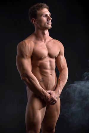 desnudo: Culturista ocultar los genitales totalmente desnudos masculinos con las manos, mirando de lejos, en el fondo oscuro Foto de archivo