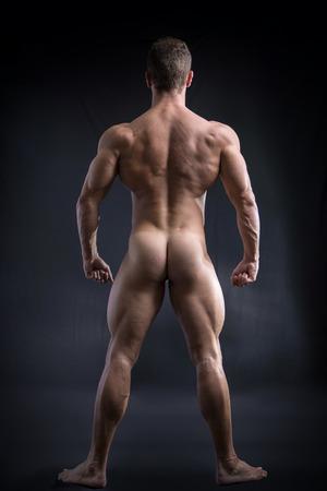 Fit Body hombre totalmente desnudo frente hacia atrás, exponiendo las nalgas y trasera, sobre fondo oscuro.