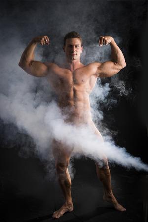 homme nu: Bodybuilder mâle totalement nue avec de la fumée cachant des organes génitaux, regardant la caméra, sur fond sombre