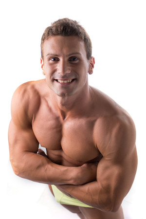 pectorals: Handsome shirtless bodybuilder shot from above, standing isolated on white background