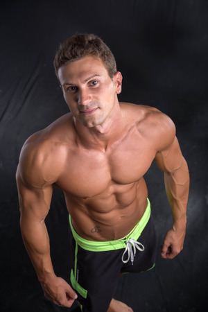 pectorals: Handsome shirtless bodybuilder shot from above, standing on dark background wearing trunks