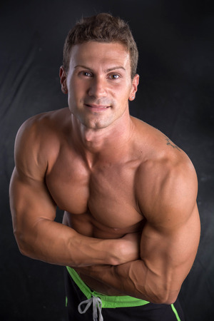 pectorals: Handsome smiling shirtless bodybuilder shot from above, standing on dark background wearing trunks Stock Photo