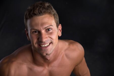 pectorals: Head and shoulder shot of shirtless handsome young man smiling at camera, on dark background