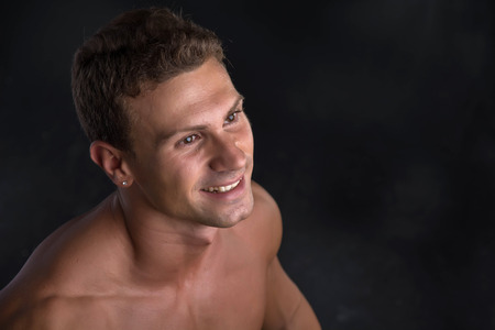 pectorals: Head and shoulder shot of shirtless handsome young man smiling, on dark background