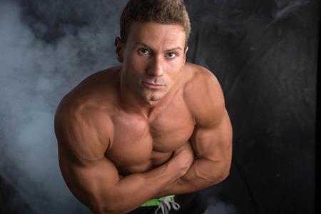 pectorals: Handsome shirtless bodybuilder shot from above, standing on dark background wearing trunks