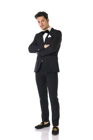 lazo negro: Hermoso hombre joven y elegante con traje y pajarita, tiro de larga duración, aislado en blanco Foto de archivo