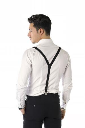 Terug van de knappe elegante jonge man met een pak, bretels en bow-tie, geïsoleerd op wit, op zoek naar camera