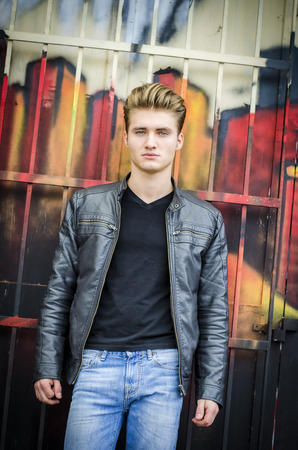 blond haired: Attractive blond haired young man standing against graffiti wall, looking at camera