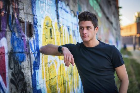 grafitis: Atractivo joven de pie contra la pared de graffiti colorido, mirando a otro lado