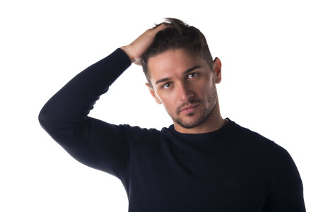 Attractive young man headshot looking at camera, touching his hair, isolated on white