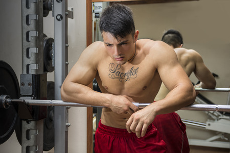 workouts: Tired muscular shirtless young male bodybuilder resting on barbell between workouts in gym Stock Photo