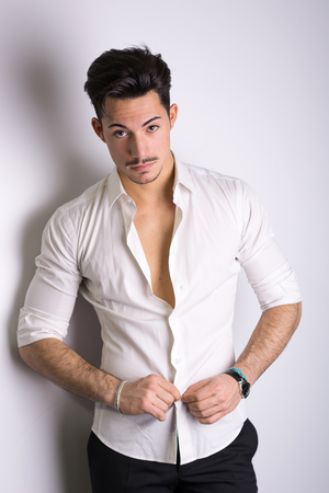 Elegant attractive young man with white shirt, leaning against wall, looking at camera photo