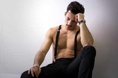 black pants: Shirtless athletic young man with suspenders and black pants sitting on floor, looking down sad