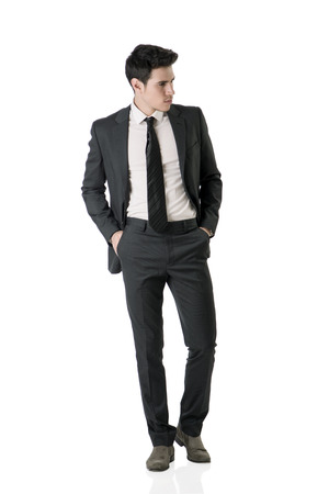 full figure: Full figure shot of handsome elegant young man with business suit and neck-tie, isolated on white, looking to a side Stock Photo