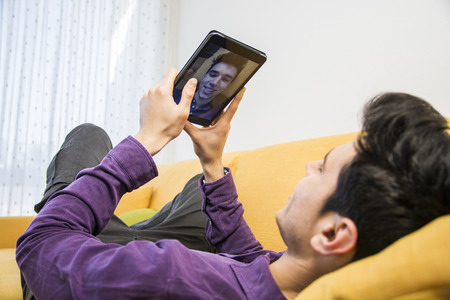 taking video: Sexy handsome young man laying indoors  taking selfie or video chatting with tablet PC smiling for the camera