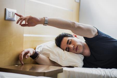 疲れてハンサムな男切り替えオフの光ながら横になっている閉じた目とベッドの上の彼の側に。
