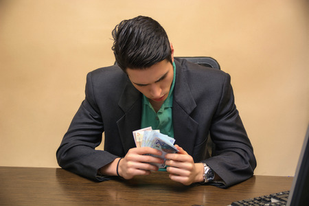 worktable: Close up Serious Young Businessman, Sitting at his Worktable, Counting Cash on Hand Seriously. Stock Photo